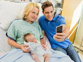 Mid adult man with woman and newborn babygirl taking selfportrait through mobile phone in hospital r