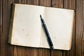 top view of old open book with fountain pen on wooden table