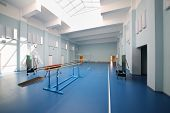 Empty school gymnasium with blue floor and gymnastic apparatus.