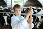 Boy in white robe stands with hayfork near small calves at large cow farm.