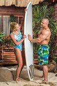 Muscular man and beautiful girl on a sandy beach with a surfboard