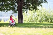Little cute girl rides on toy car on grass near big trees at sunny day.