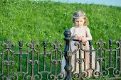 Little girl in pink puffy gown stands near black wrought-iron fence