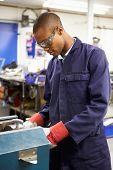 Apprentice Engineer Working On Factory Floor