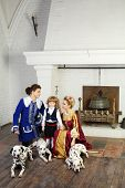 Young father, mother in medieval costumes look at little son near fireplace with three dalmatians on