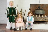 Two boys and girl in medieval costumes pose near fireplace with boiler.