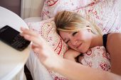 Teenage Girl Waking Up In Bed And Turning Off Alarm On Phone