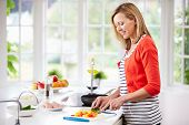 Woman Standing At Counter Preparing Meal In Kitchen