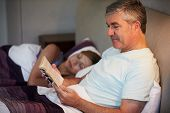 Middle Aged Couple In Bed Together With Man Reading Book