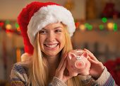 Teenage Girl In Santa Hat Showing Piggy Bank In Christmas Decora