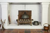 Medieval white fireplace with hanging metal pot and logs in studio.
