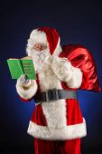 Traditional Santa Claus reading a list of good boys and girls in his notebook. Christmas.