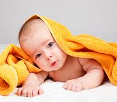 Little baby girl lying under yellow towel