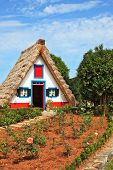 Charming white cottage with a thatched roof and gable small garden with flowers. Picturesque house-museum of the first colonists to Madeira.
