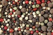 A mixture of different kinds of peppercorns, including black, white, green, grey, pink and Jamaican