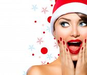 Christmas Woman. Beauty Model Girl in Santa Hat isolated on White Background. Funny Laughing Surprised Woman Portrait. Open Mouth. True Emotions. Red Lips and Manicure. Beautiful Holiday Makeup.  mouse pad
