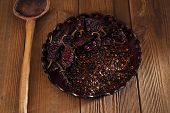 chipotle - jalapeno smoked chili flakes and whole in leather bowl,  shallow dof