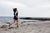 Fit Young Woman Jogging Along Shoreline