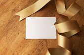Curled gold ribbon and a sheet of blank paper for your message, on old wooden desk.