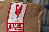 picture of fragile sign  - Fragile Handle With Care Sign On A Damaged Package
