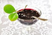 picture of chokeberry  - Chokeberry Plum Jam in a Bowl Decorated with Green Leaves - JPG