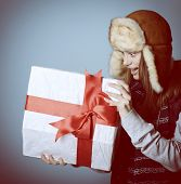 Portrait of attractive excited christmas girl in winter hat opening gift box, over blue, toned