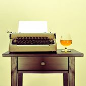 an old typewriter with a blank page and a brandy snifter with liquor on a desk, with a retro effect