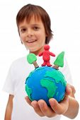 Life in harmony with nature concept - boy holding earth globe with trees and man made of colorful cl