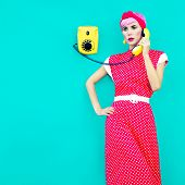 Retro fashion girl talking on a vintage telephone