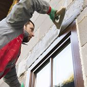 stock photo of trowel  - Plasterer spreading out plaster with trowel around the windows - JPG