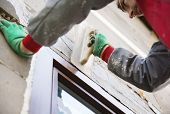 image of spreader  - Plasterer spreading out plaster with trowel around the windows - JPG