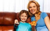 Kid switching TV and mother with pizza