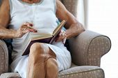 elderly woman reading her book hands anonymous