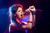 stock photo of pop star  - Young pop star girl singing on stage close up - JPG