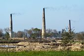 picture of belching  - Belching chimneys rise from kilns in Uttar Pradesh India - JPG
