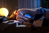 picture of nervous breakdown  - Tired businessman sleeping on sofa at home surrounded by paperwork - JPG