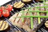 Grilled carp fillet on grill with egg plant.