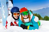 Cuddling couple in ski masks lying on the snow