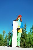 Girl in ski mask standing with snowboard