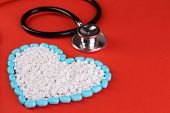 Heart of pills and stethoscope on red background