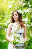Portrait Of A Beautiful Young Woman In A Wreath Of Spring Flowers With A Bouquet Of Red Tulips In Hi
