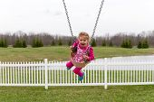 Beautiful Excited Little Girl On A Swing
