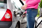 picture of gasoline station  - Closeup of woman pumping gasoline fuel in car at gas station. Petrol or gasoline being pumped into a motor vehicle car.