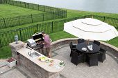 stock photo of braai  - High angle view of a man cooking meat on a gas BBQ standing in the sunshine on a paved outdoor patio at the summer kitchen preparing for guests with a table and chairs with a garden umbrella alongside - JPG