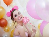 Image of smiling comely girl posing with lollipop