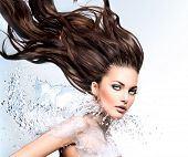 Fashion model Woman with water splash. Long blowing brown hair. Fantasy Girl. Mermaid. Fresh Water splashing on lady's body