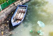 picture of dock a pond  - Old plastic boat in the pond of urban park - JPG