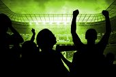 Silhouettes of football supporters against large football stadium with brasilian fans