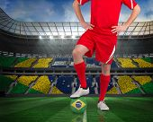 Composite image of football player standing with brasil ball against large football stadium with brasilian fans