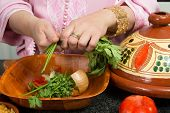 Hands of a woman adding vegetables to a traditional Moroccan tajine during Ramadan nights (Moroccan